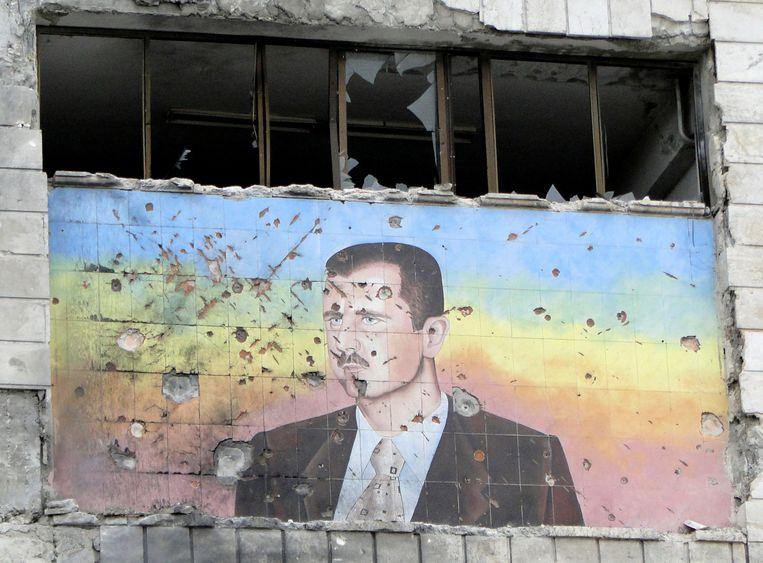 Een portret van de Syrische president Bashar al-Assad op een kapotgeschoten gebouw in Aleppo. Ooit leken de dagen van Assad geteld, maar nu herrijst hij uit de as. Beeld REUTERS