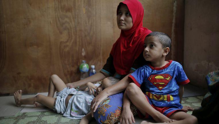 Een moeder met twee kinderen, gevlucht uit Birma en nu in Kuala Lumpur. Beeld epa