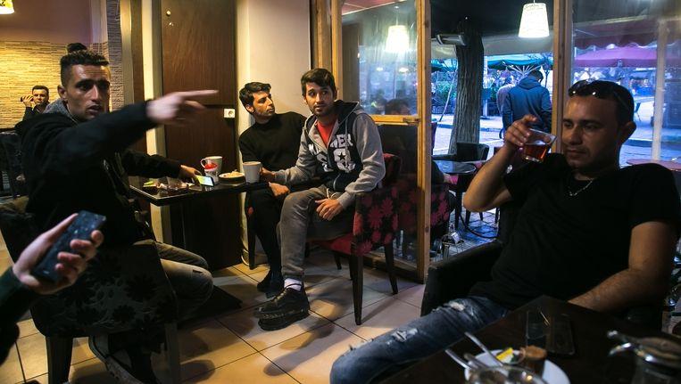 Reza (rechts) zit met lotgenoten uit Iran in een bar aan het Victoriaplein in de Griekse hoofdstad Athene. Beeld Nicola Zolin