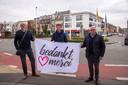 Kristof, Ignace en burgemeester Alain Pardaen hijsen de eerste Bedankt Merci vlag aan het Felix Beernaertsplein in Wetteren.