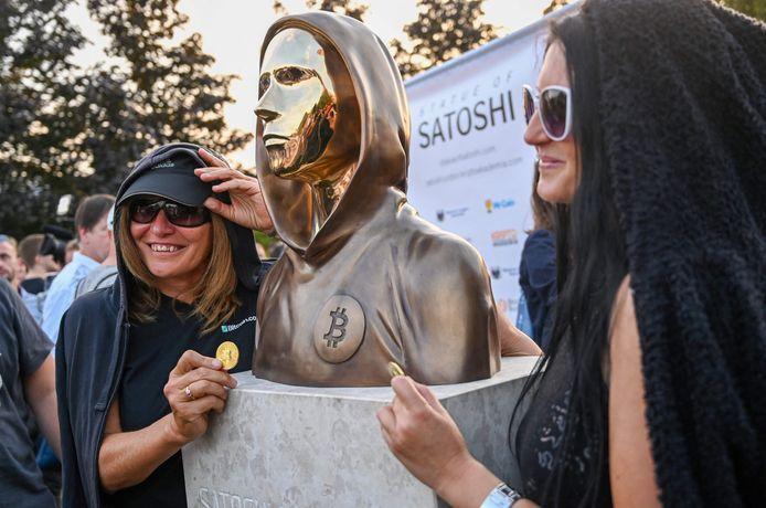 Bitcoin-fans poseren bij het pas onthulde standbeeld.