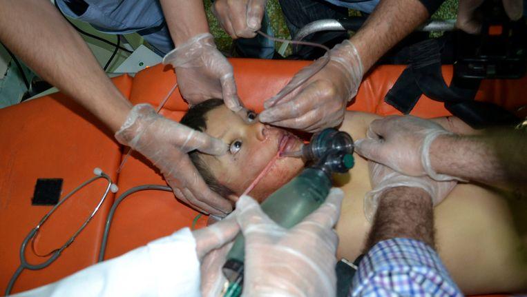 Een jongen die, volgens oppositiebronnen, chloorgas heeft ingeademd wordt behandeld in een ziekenhuis aan de Turkse grens. Beeld reuters