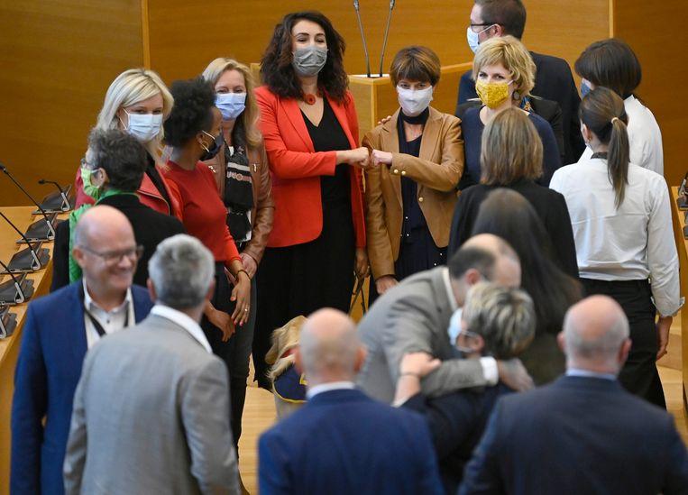 Christie Morreale (PS), Valérie De Bue (MR) en Céline Tellier (Ecolo) steunen elkaar in het Waalse parlement. Beeld Photo News