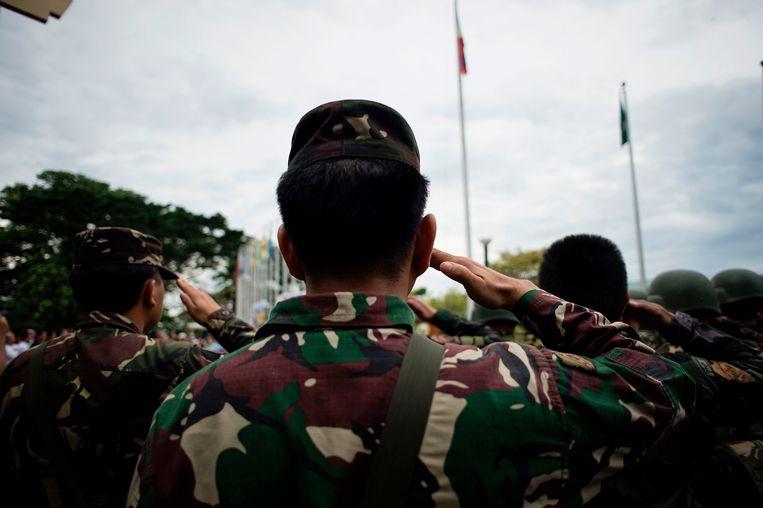 Filippijnse soldaten salueren terwijl de vlag wordt gehesen boven het stadhuis van Marawi. Het leger strijdt al weken tegen jihadisten die de stad bezet houden. Beeld AFP Noel Celis