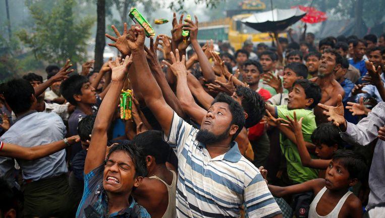 Rohingya proberen etenswaren te vangen die door weldoeners in de menigte worden gegooid in Cox's Bazar Beeld REUTERS
