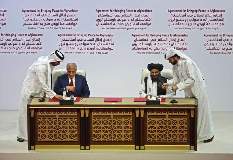 VS-afgevaardigde Zalmay Khalilzad en talibanleider Mullah Abdul Ghani Baradar ondertekenen het vredesakkoord.