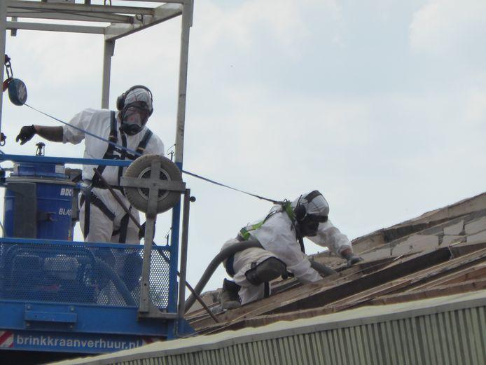 In speciale pakken halen bedrijven asbest van het dak.