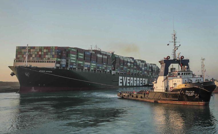 Een sleepboot trekt de Ever Given uit de blubber in het Suezkanaal. Beeld AP