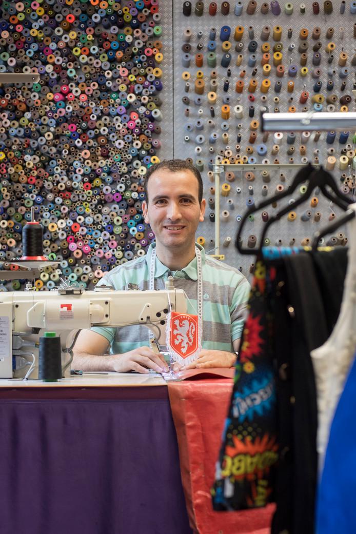 Hassan Ahannach achter zijn naaimachine met het vaantje van Wil van Rhee.