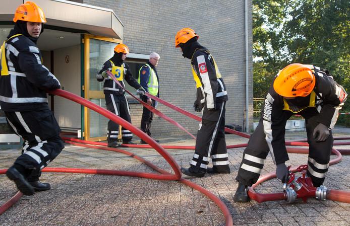 De aspiranten van korps Dalfsen rollen de slangen uit om het denkbeeldige vuur bij het Hardenbergse verzorgingstehuis te bestrijden.