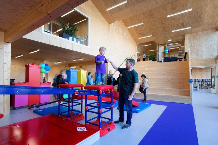Brent speelt samen met zijn vader op de speeltoestellen in het nieuwe gebouw.