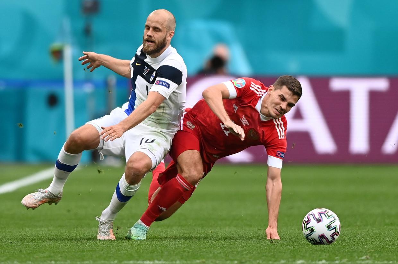 De Finse sterspeler Teemu Pukki (l.) en de Rus Roman Zobnin gaan neer na een duel, in Sint-Petersburg. Beeld EPA