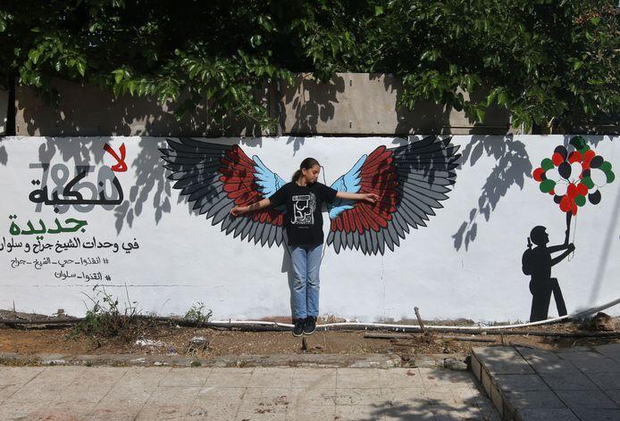 Een meisje poseert voor een graffititekening in oost-Jeruzalem.