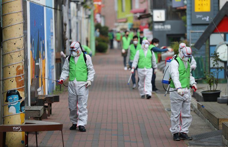 Gezondheidswerkers desinfecteren een straat in Zuid-Korea.
