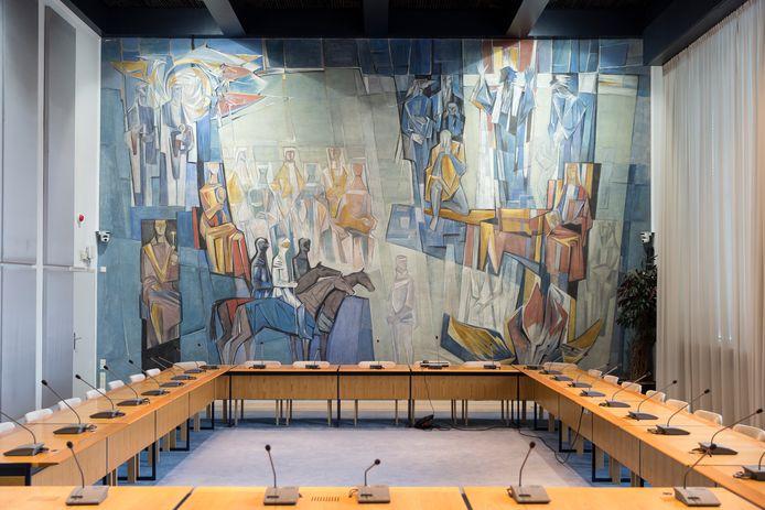 Foto van de oude raadzaal: De 'stemmen uit het verleden', wandschildering in de raadzaal van het gemeentehuis in Zevenaar. De namen van de figuren op de muur staan vermeld op de bronzen klokken van het carillon.