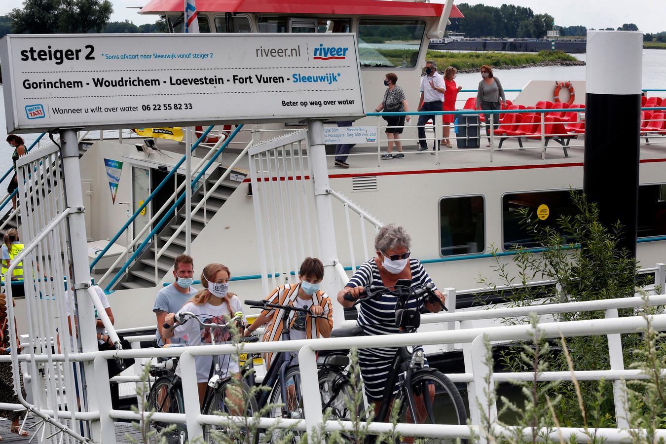 Juni 2020: passagiers, allemaal met een mondkapje, verlaten een pont van Riveer. De veerdienst hervat 1 maart de reguliere dienstregeling.