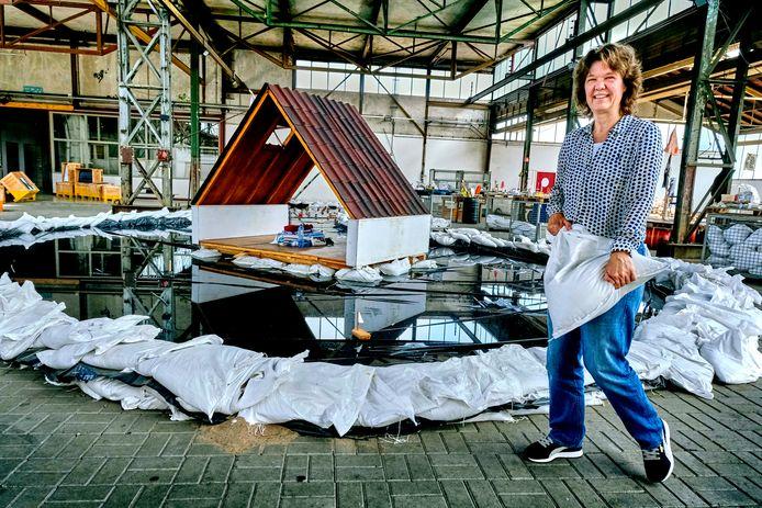 Ellen Kelder, opgavemanager bij de gemeente, bij de tentoonstelling 'Klaar voor de Staart'. Met in het midden een grote plas water een een zolder, mét noodpakket.