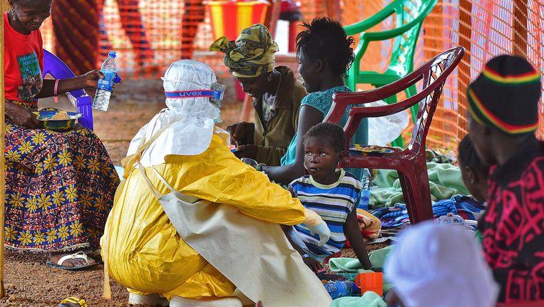 Een medewerker van een gezondheidsorganisatie in Kailahun helpt een jong slachtoffer. Kailahun en Kenama vormen het epicentrum van de ebola-uitbraak. De gezondheidsorganisaties kunnen de hulpvraag niet aan. Beeld AFP