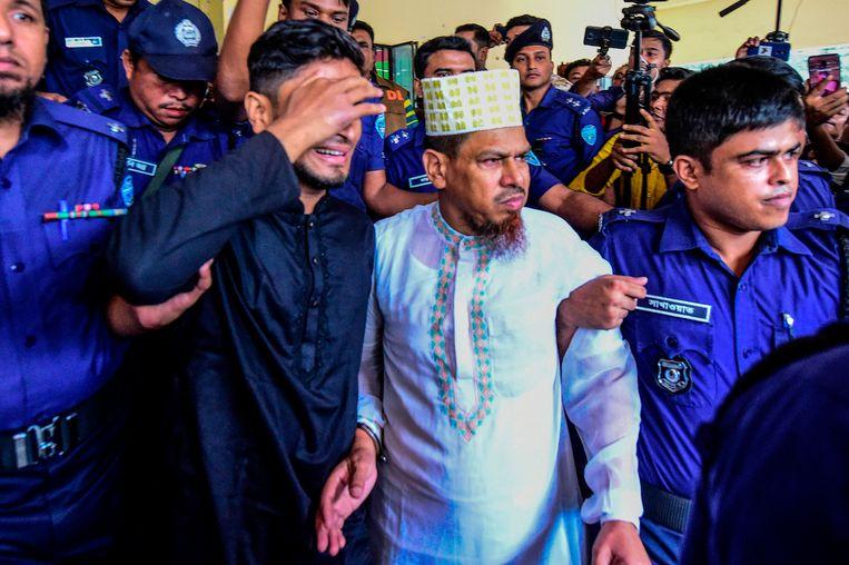 Schoolhoofd en hoofdverdachte Siraj Ud Doula (midden) wordt naar buiten gebracht nadat het oordeel is geveld. Beeld AFP