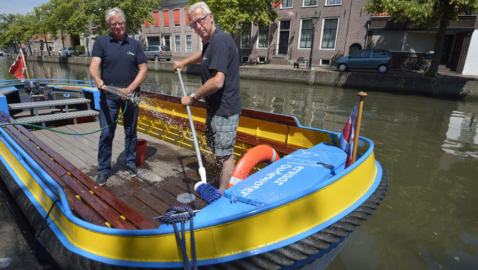 Piet Six en Theo Boere maken het schip schoon voor de komst van de Koning
