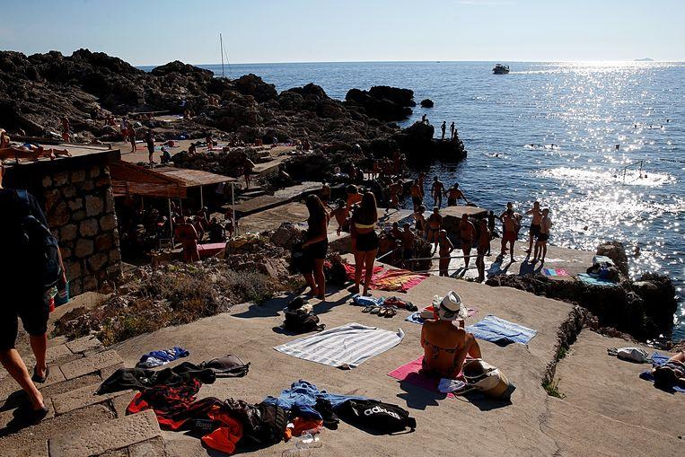 Toeristen aan het strand van Dubrovnik, Kroatië.  Beeld Getty Images