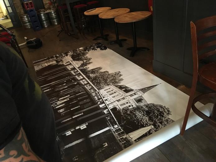 Een metershoge foto van de Hoge Brug bij de Haven - hier nog uitgerold op de grond - komt achter de bar te hangen.