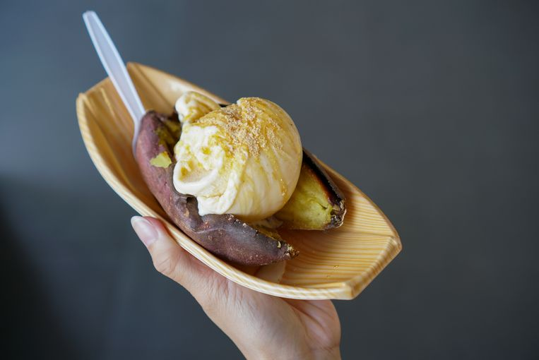 Hand holding a bowl of sweet potato topped vanilla ice cream and maple syrup. (isolated) Beeld Getty Images/iStockphoto