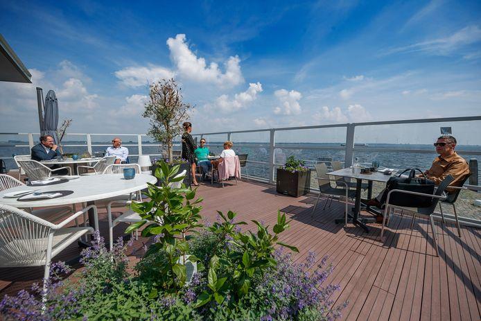 De architect lijkt de eetzaal en het zomerse terras te hebben ontworpen met het oog op corona: dertig gasten ontspannen hier fijn én verantwoord.