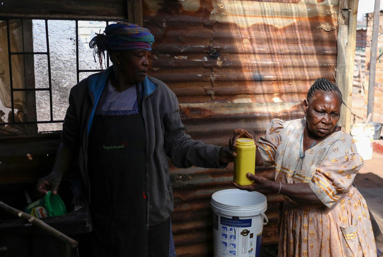 Ook populair werd het zelf brouwen van bier op basis van maïs en sorghum. Met verkoop aan huis, zoals hier in Soweto. Beeld Reuters