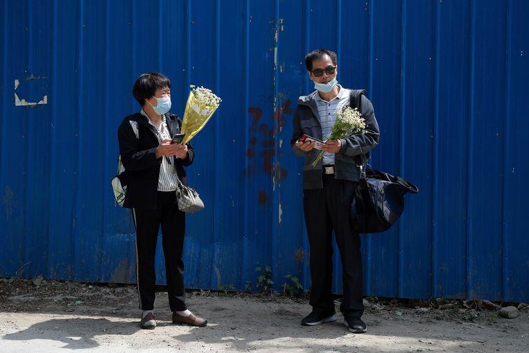 De moeder van Chen Mei (l) praat met de vader van Cai Wei buiten de rechtbank. Hun kinderen stonden terecht voor onder meer het herpubliceren van dagboeken van inwoners van Wuhan ten tijde van de coronauitbraak.  Beeld AP