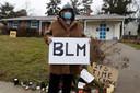 Een demonstrant met een bord met de tekst 'Black Lives Matter' voor het huis waar Andre Hill werd doodgeschoten.