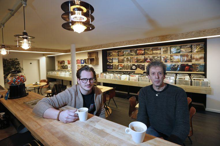 Joris Jaenen (met bril) en Albert Claesen aan hun houten toog met een tasje koffie. Op de achtergrond de houten bakken met zo'n 4.000 lp's op vinyl.