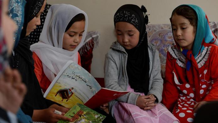 Een Afghaans meisje leest aan haar vriendjes de vertaalde versie voor van Toen Rorors Bed de Lucht In Vloog. Dat doet ze in een leeshoekje dat is ingericht bij mensen thuis in een buitenwijk van Kabul.