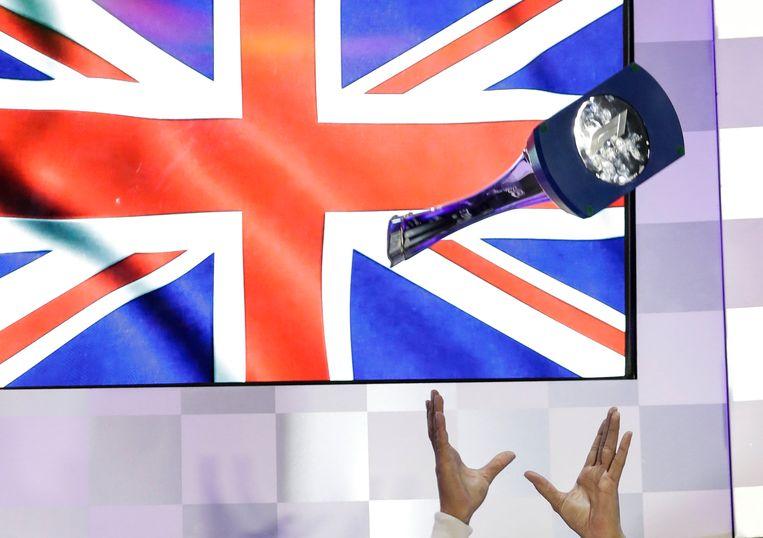 Wereldkampioen Lewis Hamilton gooit zijn trofee omhoog na de grote prijs van Abu Dhabi. Beeld EPA
