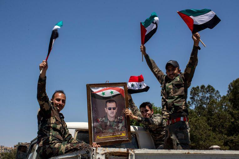 Syrische strijders tonen een portret van president Bashar al Assad.  Beeld AP