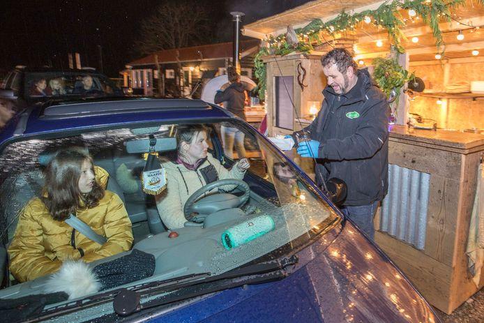 Lau Goud geeft Sharon de Leeuw (achter het stuur) haar bestelling. Op de achtergrond staat dochter Femke bij de pizza-oven.