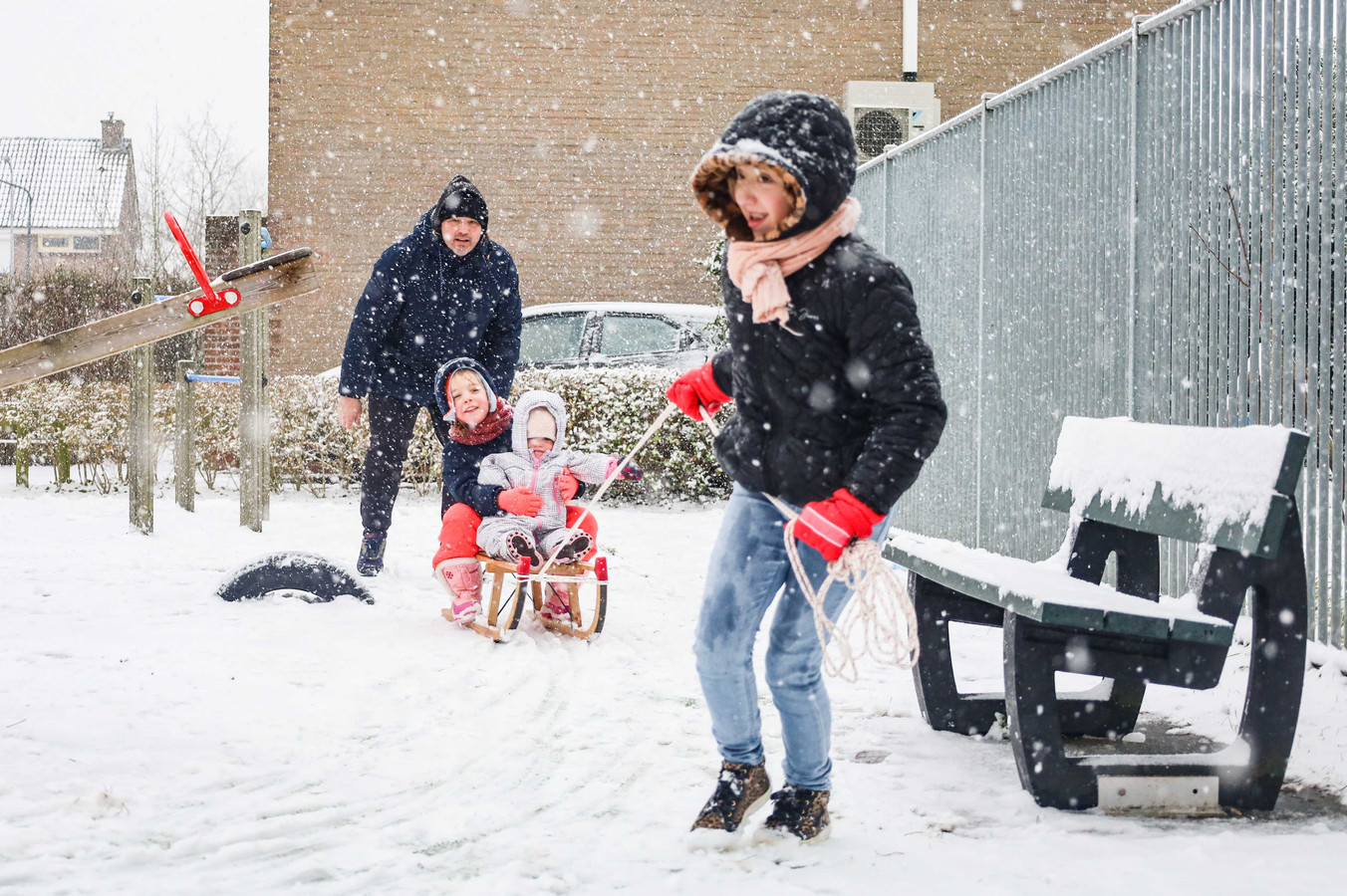 Kinderen en hun ouders spelen met een slee in de sneeuw.