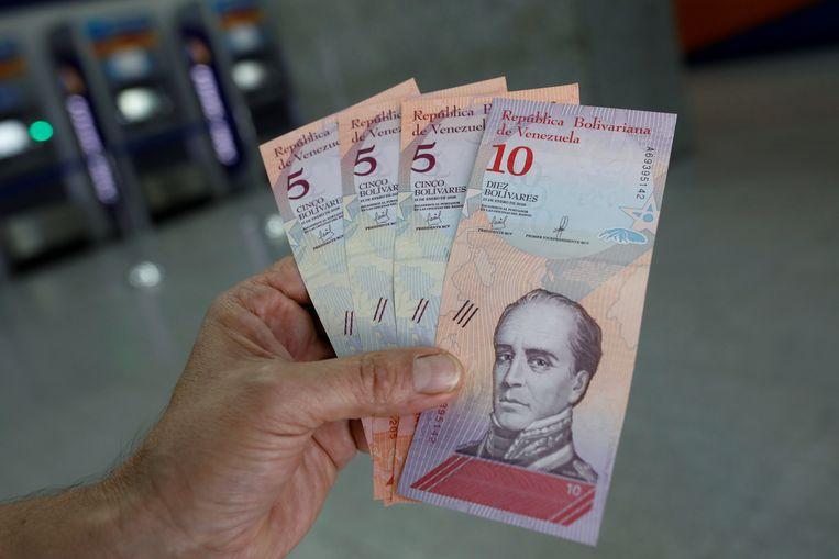 Een man toont de nieuwe briefjes van de Venezolaanse bolivar. Er zijn vijf nullen op geschrapt.  Beeld REUTERS