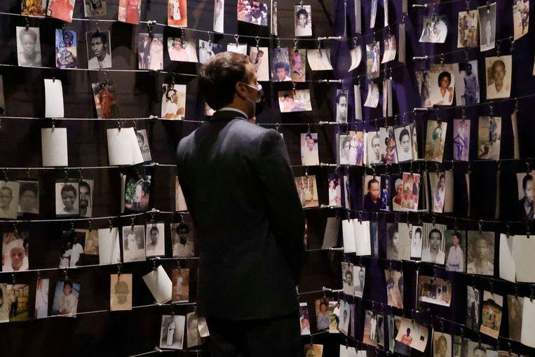 De Franse president Emmanuel Macron kijkt naar foto's van slachtoffers van de genocide in Rwanda tijdens zijn bezoek aan de hoofdstad Kigali. Beeld AFP