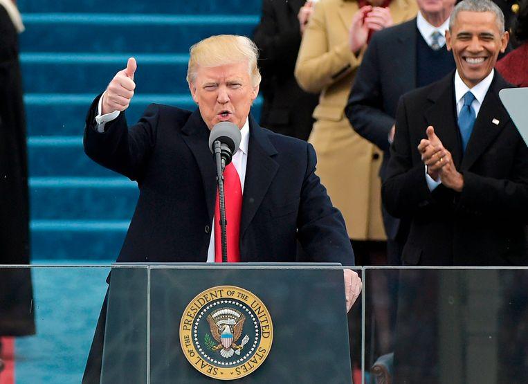 Donald Trump tijdens zijn eigen inauguratie in 2017, met Barack Obama op de achtergrond. Beeld AFP