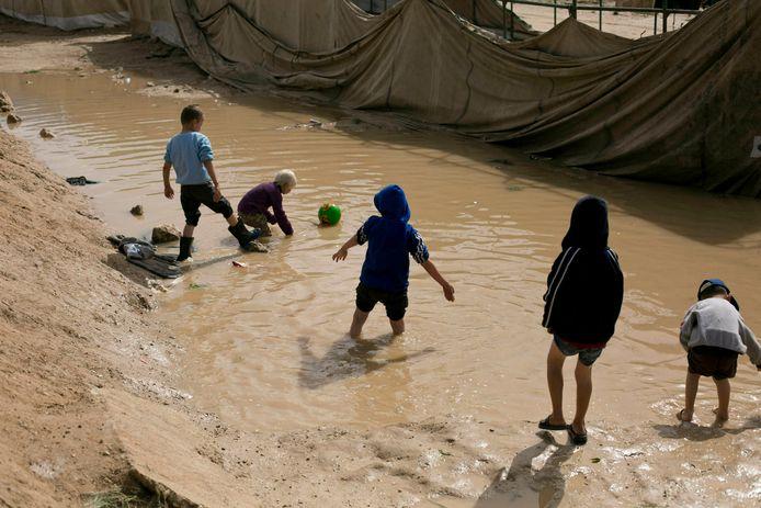 Kinderen spelen in een modderpoel in het Al-Holkamp in Syrië.