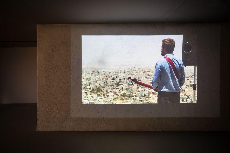 Daniel Kiczales ging met zijn Fender en geluidsinstallatie naar de top van de Scopusberg, Oost-Jeruzalem, met uitzicht over de Palestijnse wijk Al-Issawiya. En speelde daar zijn vingers blauw. Beeld Natascha Libbert