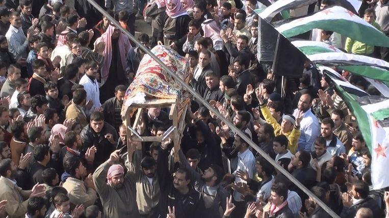 Syrische demonstranten dragen de kist van een demonstrant gedood tijdens rellen vlakbij Homs. Beeld reuters