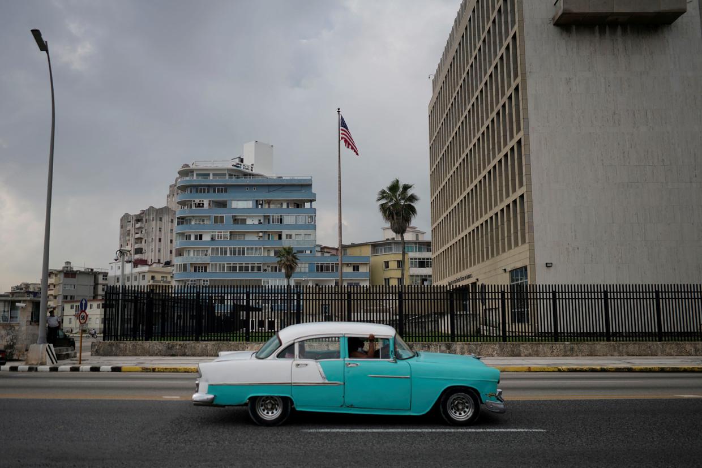 Een vintage wagen passeert de Amerikaanse ambassade in Havana, hoofdstad van Cuba. Beeld REUTERS