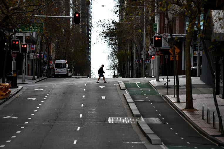 Een voetganger in het verlaten centrum van miljoenenstad Sydney, die al vijf weken in lockdown is. Beeld EPA