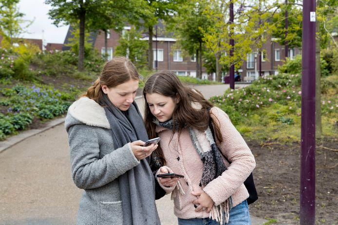 Studenten Maaike van der Sterre (links) en Maij Boeijen van De Kempel zoeken in het Weverspark uit hoeveel ingangen er zijn tijdens de activiteitenweek van de lerarenopleiding.