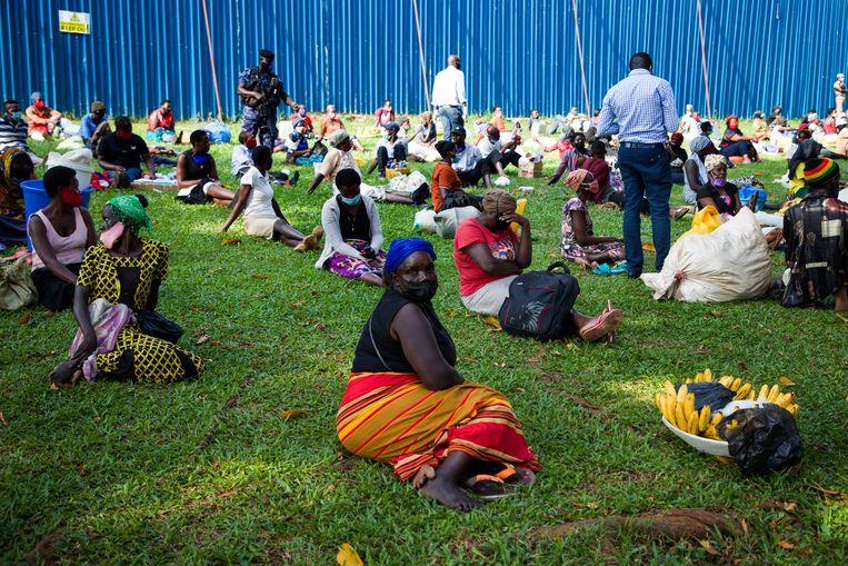 Op een veld in Kampala zitten allemaal verkopers die door de politie zijn aangehouden. Beeld Katumba Badru