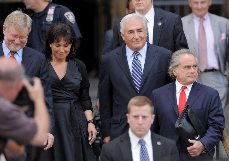 Een tevreden DSK verlaat samen met zijn vrouw Anne Sinclair en advocaat Benjamin Brafman het gerechtsgebouw in Manhattan. Beeld AFP