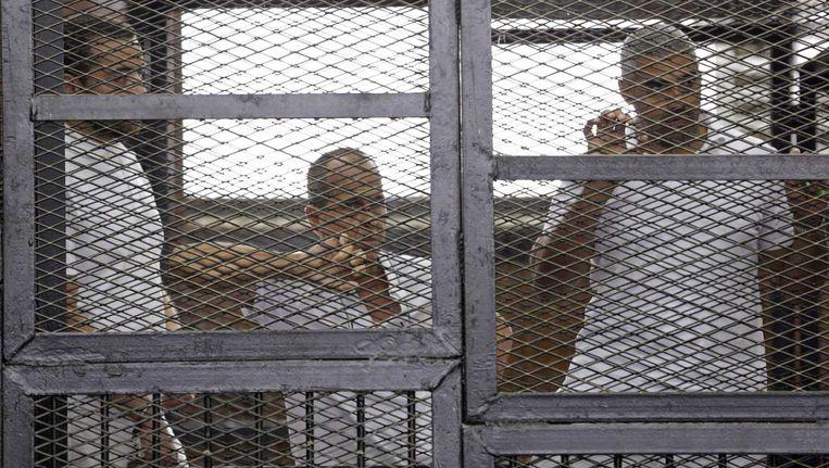De drie veroordeelde journalisten in de verdachtenkooi van de rechtbank in Caïro. Beeld reuters