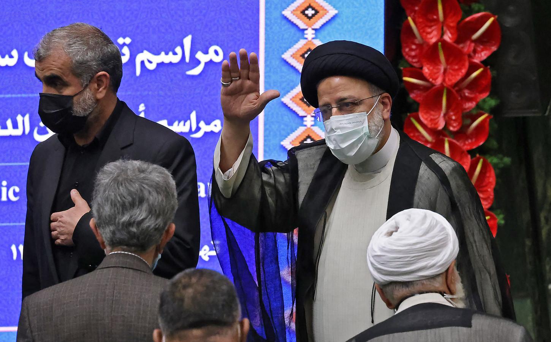 De nieuwe Iraanse president Ebrahim Raisi (R) zwaait bij zijn aankomst in het parlement.